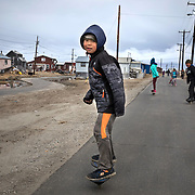 A young boy rides a rip-stick down the street in Shishmaref, Alaska, an Inupiat community of about 600 people near the Bering Strait, Only one quarter mile wide and two and half miles long, Shishmaref has been  grappling with rising sea levels that have eroded more than 200 feet of the village, since 1969, according to a relocation study published in February. Climate change has resulted in a reduction in the sea ice which buffers Shishmaref from storm surges. At the same time, the permafrost that the village is built on has also begun to melt, making the shore even more vulnerable to erosion. The Inupiat rely heavily on a subsistence lifestyle, hunting and gathering much of their food. Shishmaref is one of at least 31 Alaska Native villages under imminent threat due to climate change, according to a 2009 report from the Government Accountability Office.
