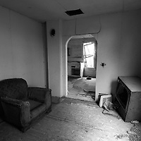 Seat and television in small room in derelict home USA