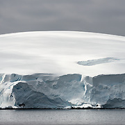 The gently domed top of a glacier contrasts with the jagged ice cliff where it meets the waterline near Melchior Island on the Antarctic Peninsula.