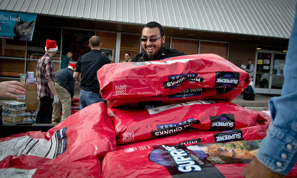 mkb120116f/biz/Marla Brose/120116<br /> Armando Holguin, an animal control officer in Valencia County, lifts big bags of dog food onto a trailer, during Long Leash on Life's pet food donation distribution, at the pet health food and supply store in Albuquerque. Long Leash on Life donated about 150,000 pounds of dog and cat food to 34 rescue organization and animal food banks, Thursday, Dec. 1, 2016 in their second annual pet food drive. (Marla Brose/Albuquerque Journal)