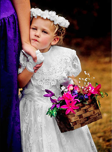 Waterville, Maine. A young girl who was acting as a flower girl awaits a wedding to begin.