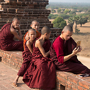 Myanmar (Burma). Bagan. Young novices visit a temple and take selfies.