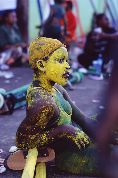 "Trinidad and Tobago ""MOKO JUMBIES: The Dancing Spirits of Trinidad"".(Ferlyn Frank is completely covered  in body paint while waiting for a parade to continue.).A photo essay about a stilt walking school in Cocorite, Trinidad..Dragon Glen de Souza founded the Keylemanjahro School of Art & Culture in 1986. The main purpose of the school is to keep children off the streets and away from drugs..He first taught dances like the Calypso, African dance and the jig with his former partner Cathy Ann Samuel.  Searching for other activities to engage the children in, he rediscovered the art of stilt-walking, a tradition known in West Africa as the Moko Jumbies , protectors of the villages and participants in religious ceremonies. The art was brought to Trinidad by the slave trade and soon forgotten..Today Dragon's school has over 100 members from age 4 and up..His 2 year old son Mutawakkil is probably the youngest Moko Jumbie ever. The stilts are made by Dragon and his students and can be as high as 12-15 feet. The children show their artistic talents mostly at the annual Carnival, which today is unthinkable without the presence of the Moko Jumbies. A band can have up to 80 children on stilts and they have won many of the prestigious prizes and trophies that are awarded by the National Carnival Commission. Designers like  Peter Minshall , Brian Mac Farlane and Laura Anderson Barbata create dazzling costumes for the school which are admired by thousands of  spectators. Besides stilt-walking the children learn the limbo dance, drumming, fire blowing and how to ride  unicycles..The school is situated in Cocorite, a suburb of Port of Spain, the capital of Trinidad and Tobago..all images © Stefan Falke"
