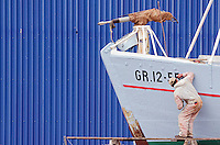 Colorful blue wall and fishing vessel being painted in Sisimiut Greenland