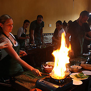 A tourist sets fire to her pan while preparing food at a Vietnamese cooking class run by renowned Vietnamese chef Ms Trinh Diem Vy at her restaurant The Morning Glory, Hoi An, Vietnam. Hoi An is an ancient town and an exceptionally well-preserved example of a South-East Asian trading port dating from the 15th century. Hoi An is now a major tourist attraction because of its history. Hoi An, Vietnam. 5th March 2012. Photo Tim Clayton