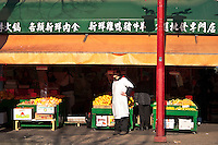 Green grocer stands in front of shop, Chinatown, Vancouver BC