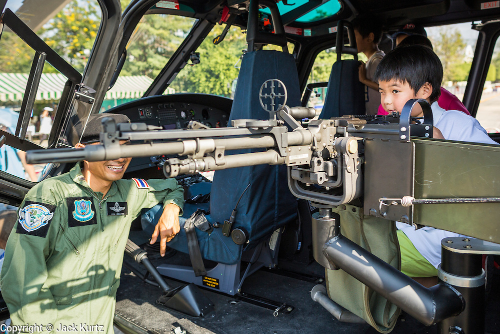 """11 JANUARY 2014 - BANGKOK, THAILAND: A boy looks at a machine gun in a Thai army helicopter during Children's Day. The Royal Thai Army hosted a """"Children's Day"""" event at the 2nd Cavalry King's Guard Division base in Bangkok. Children had an opportunity to look at military weapons, climb around on tanks, artillery pieces and helicopters and look at battlefield medical facilities. The Children's Day fair comes amidst political strife and concerns of a possible coup in Thailand. Earlier in the week, the Thai army announced that movements of armored vehicles through Bangkok were not in preparation of a coup, but were moving equipment into position for Children's Day.      PHOTO BY JACK KURTZ"""