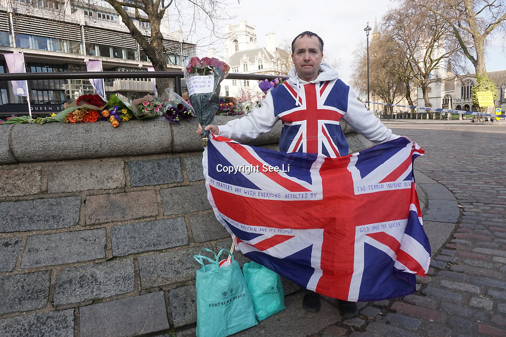 Westminster, London, UK. 23rd Mar, 2017. With his flag and a bunch of roses, John Loughrey of Streatham mourns those killed and injured in Tuesday's knife attack on Westminster Bridge and in the grounds of Parliament, in which three people and their attacker were killed with over 40 injured. Credit: See Li