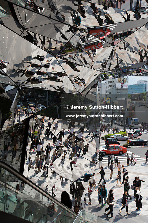 Shoppers descend the escalators, in the multi-faceted mirrored entrance way to the recently opened 'Tokyu Plaza Omotesando Harajuku' shopping complex in Harajuku district, in Tokyo, Japan on Friday 11th May 2012. Designed by architect Hiroshi Nakamura