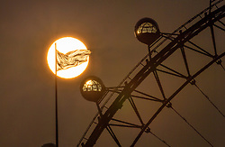 © Licensed to London News Pictures. 14/09/2020. London, UK. The sun rises behind a Union flag fluttering over Whitehall and The London Eye ferris wheel. Warm weather and high temperatures are expected in parts of the UK this week. Photo credit: Peter Macdiarmid/LNP