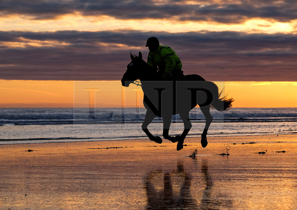 © Licensed to London News Pictures. <br /> 07/04/2017<br /> Saltburn-by-the-Sea, UK. <br />  <br /> A rider and his horse gallop along the beach as the sun rises at Saltburn-by-the-Sea in North Yorkshire. <br /> <br /> <br /> Photo credit: Ian Forsyth/LNP