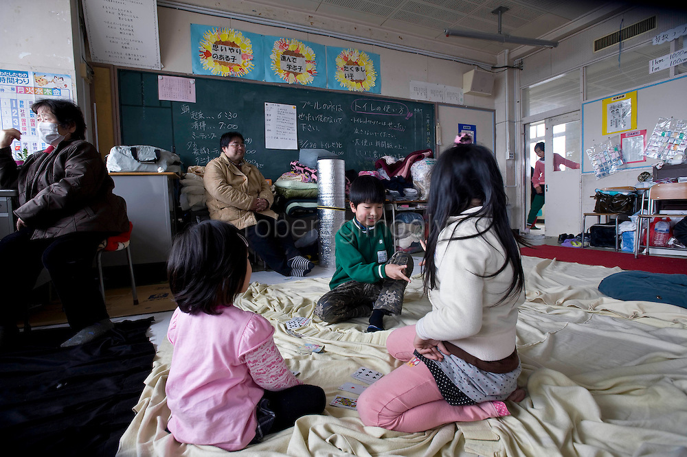 Children play cards in the classroom of an elementary school that has been turned into a shelter in Ishinomaki, Japan on 15 March, 2011.  Photographer: Robert Gilhooly
