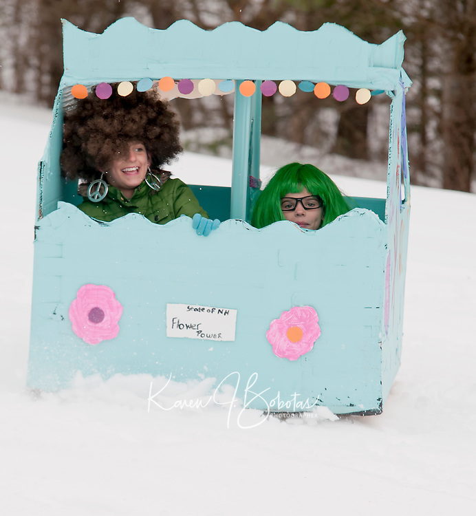 Avy and Mykynzy Bartlett bring out the sixties with their Flower Power vehicle as they rock and roll down the Gilford Outing Club sliding hill for the annual Gilford Parks and Recreation cardboard sled derby Wednesday morning.  (Karen Bobotas/for the Laconia Daily Sun)