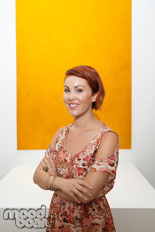 Half-length portrait of young woman in front of yellow painting