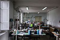 """SOVERIA MANNELLI, ITALY - 17 NOVEMBER 2016: A woman is a work here in the textile workshop of the Lanificio Leo woolen mill in Soveria Mannelli, Italy, on November 17th 2016.<br /> <br /> Lanificio Leo was the first and last machine-operated woolen mill of Calabria, founded in 1873, it employed 50 people until the 1970s, when national policies to develop Italy's South cut out small businesses and encouraged larger productions or employment in the public administration.<br /> <br /> The woolen mill was on stand-by for about two decades, until Emilio Salvatore Leo, 41, started inviting international designers and artists to summer residencies in Soveria Mannelli. With their inspiration, he tried to envision a future for his mill and his town that was not of a museum of the past,<br /> Over the years, Mr. Leo transformed his family's industrial converter of Calabrian wool into a brand that makes design products for home and wear. His century old machines now weave wool from Australia or New Zealand, cashmere from Nepal and cotton from Egypt or South America. He calls it a """"start-up on scrap metals,"""" referring to the dozens of different looms that his family acquired over the years.<br /> <br /> Soveria Mannelli is a mountain-top village in the southern region of Calabria that counts 3,070 inhabitants. The town was a strategic outpost until the 1970s, when the main artery road from Naples area to Italy's south-western tip, Reggio Calabria went through the town. But once the government started building a motorway miles away, it was cut out from the fastest communications and from the most ambitious plans to develop Italy's South. Instead of despairing, residents benefited of the geographical disadvantage to keep away the mafia infiltrations, and started creating solid businesses thanks to its administrative stability, its forward-thinking mayors and a vibrant entrepreneurship numbering a national, medium-sized publishing house, a leading school furniture manufacturer and"""