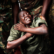 November 15th 2013, in Bangui at the funerals of Tanguy Residou, a former  FACA soldier killed by the Seleka the week before, a female soldier falls out of emotions on the ground, while her brothers in arms try to catch her.