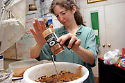 Janet, 43, one of the founders of the Freegan movement in New York is preparing a cake at a dinner cooked entirely with food recovered from dumping sites around the island of Manhattan, New York, NY., on Friday, June 23, 2006. Freegans are a community of people who aims at recovering wasted food, books, clothing, office supplies and other items from the refuse of retail stores, frequently discarded in brand new condition. They recover goods not for profit, but to serve their own immediate needs and to share freely with others. According to a study by a USDA-commissioned study by Dr. Timothy Jones at the University of Arizona, half of all food in the United States is wasted at a cost of $100 billion dollars every year. Yet 4.4 million people in the United States alone are classified by the USDA as hungry. Global estimates place the annual rate of starvation deaths at well over 8 million. The massive waste generated in the process fills landfills and consumes land as new landfills are built. This waste stream also pollutes the environment, damages public health as landfills chemicals leak into the ground, and incinerators spew heavy metals back into the atmosphere. Freegans practice strategies for everyday living based on sharing resources, minimizing the detrimental impact of our consumption, and reducing and recovering waste and independence from the profit-driven economy. They are dismayed by the social and ecological costs of an economic model where only profit is valued, at the expense of the environment. In a society that worships competition and self-interest, Freegans advocate living ethical, free, and happy lives centred around community and the notion that a healthy society must function on interdependence. Freegans also believe that people have a right and responsibility to take back control of their time.