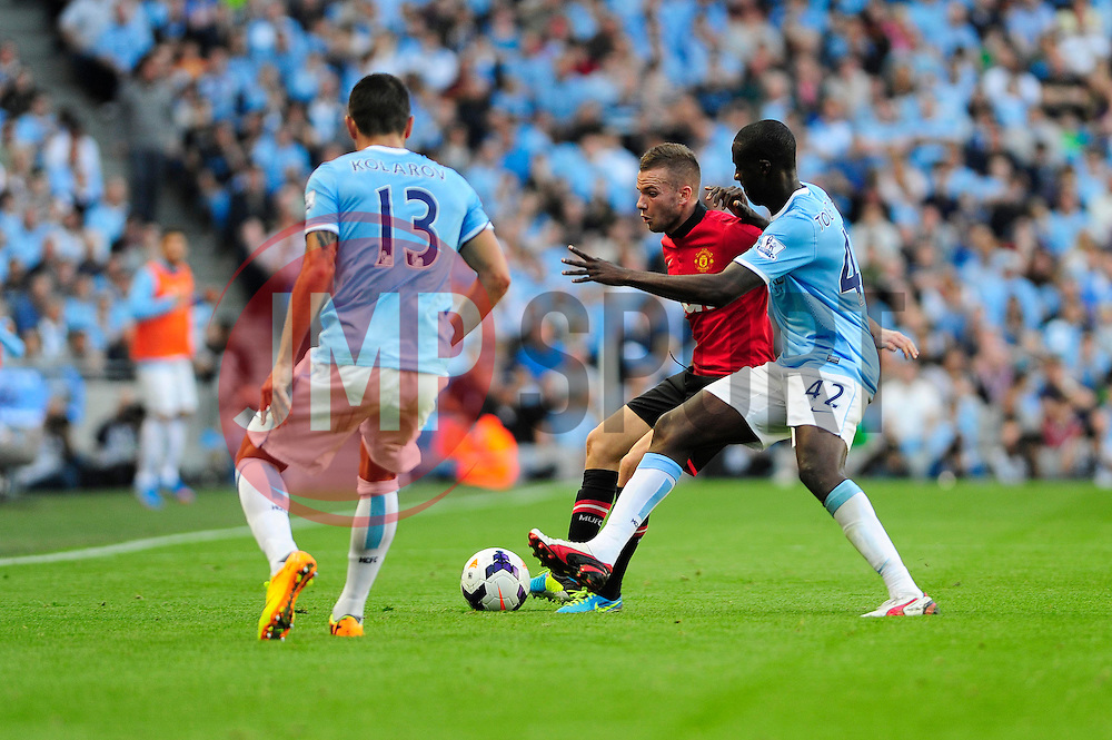 Manchester City's Yaya Toure challenges Manchester United's Tom Cleverley - Photo mandatory by-line: Dougie Allward/JMP - Tel: Mobile: 07966 386802 22/09/2013 - SPORT - FOOTBALL - City of Manchester Stadium - Manchester - Manchester City V Manchester United - Barclays Premier League