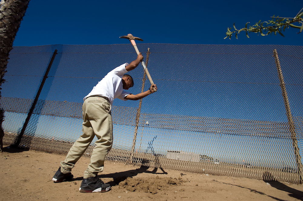 Tijuana Mexico ..a member of the activist group 'border meetup' diggs a whole in order to plant a cactus near the fence..While working on this long term project 'La Frontera' I want to examine the cultural and humanitarian activities on both sides of a border that keeps the United States and Mexico apart with a wall of steel already 600 miles long. The turf wars of drug cartels, arms trafficking and rampant kidnappings turned cities like Tijuana into some of the most dangerous places on earth. Despite the violence many brave artists, photographers, architects, poets, humanitarians, teachers etc live and work in the shadow of the wall on both sides and have a positive influence on this region; they are the focus of my long term project along the border. (Over time I plan to cover the entire length from the Atlantic to the Pacific, these images were taken in and around Tijuana).© Stefan Falke