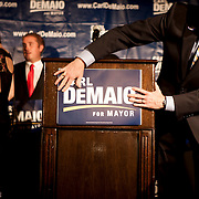 "T.J. Zane, president of the Lincoln Club of San Diego County, places a ""Carl DeMaio for Mayor"" sign on a podium before the candidate addresses supporters at the U.S. Grant Hotel."