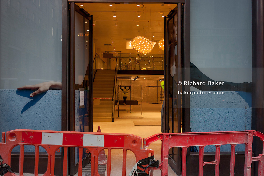 A workman seen through the open doorway of a new Jigsaw shop in central London.