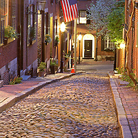 Romantic Boston cityscape photography of old colonial brick row houses along Acorn Street on a beautiful spring evening. Spring blossoms are blooming on Acorn Street near Louisburg Square, the most prestigious address in Beacon Hill. Street lanterns provide the warm night light in Beacon Hill. Acorn Street, often mentioned as the most frequently photographed street in the United States of America. It is a narrow lane paved with cobblestones that was home to coachmen employed by families in Mt. Vernon and Chestnut Street mansions.<br />