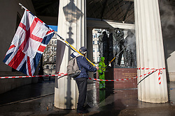© Licensed to London News Pictures. 22/01/2019. London, UK. A man carrying the Union Jack and St George's Cross flags watches as a workman cleans paint off the Canada Memorial in Green Pack after it was vandalised. Photo credit: Rob Pinney/LNP