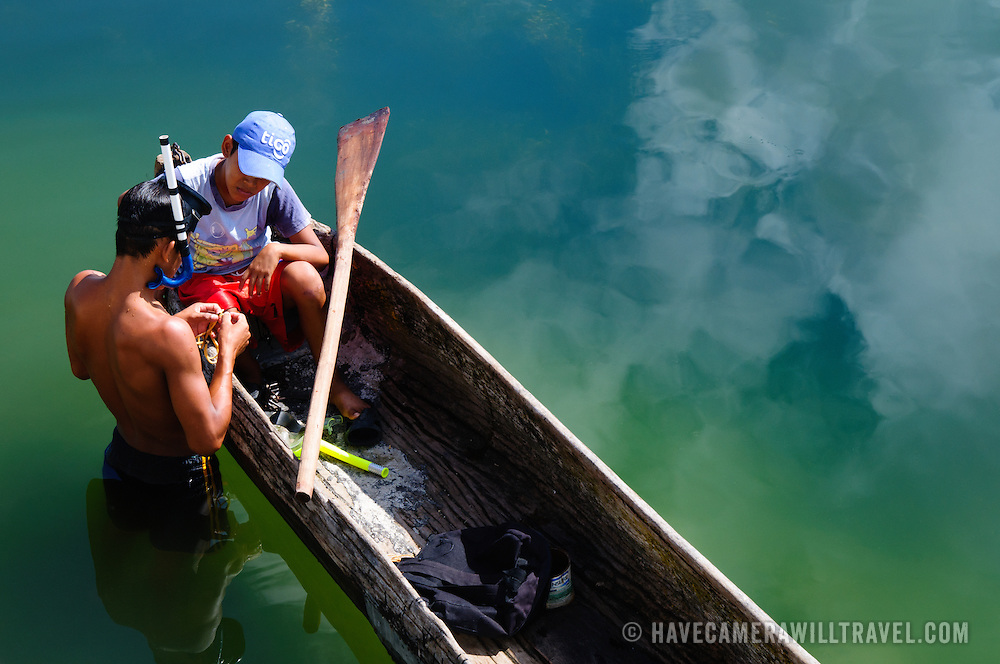 Two boys fish in Lake Peten Itza near Flores in north Guatemala. The boy standing in the shallows with the mask and snorkel is threading bait onto a hook as the other watches from the canoe.