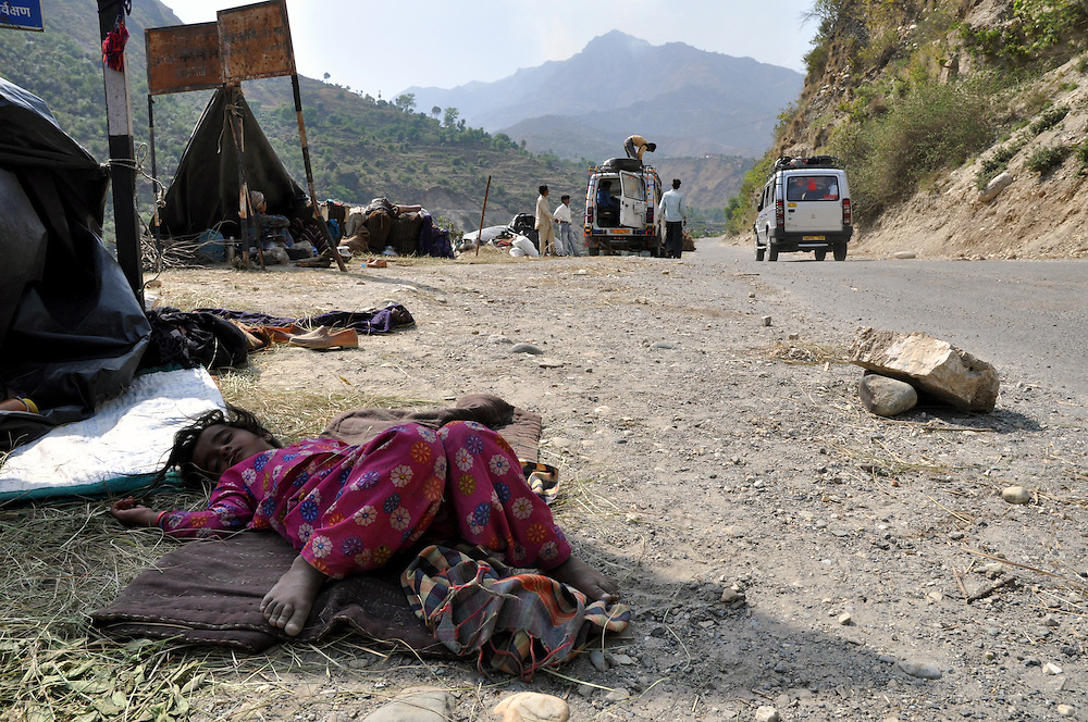 Salma, 5 years old, napping in her family's camp along the roadside.