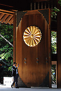 A man takes a photo with his mobile phone at the main gate of Yasukuni Shrine in Tokyo, Japan. Every year on August 15, the day Japan officially surrendered in WWII, tens of thousands of Japanese visit the controversial shrine to pay their respects to the 2.46 million war dead enshrined there, the majority of which are soldiers and others killed in WWII and including 14 Class A convicted war criminals, such as Japan's war-time prime minister Hideki Tojo. Each year speculation escalates as to whether the country's political leaders will visit the shrine, the last to do so being Junichiro Koizumi in 2005. Nationalism in Japan is reportedly on the rise, while sentiment against the nation by countries that suffered from Japan's wartime brutality, such as China, has been further aggravated by Japan's insistence on glossing over its wartime atrocities in school text books...Photographer:Robert Gilhooly....Photographer:Robert Gilhooly