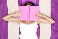 Young woman covering face with book while lying on picnic blanket