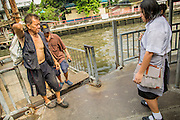 21 NOVEMBER 2012 - BANGKOK, THAILAND: People get off a pedestrian ferry on Khlong Saen Saeb, while others wait to board. There are only a few ferries that cross the Khlong. They use a winch to pull the boat across the Khlong. The fare is 2 Thai Baht, about $0.10 (US). Bangkok used to be criss crossed by canals (called Khlongs in Thai) but most have been filled in and paved over. Khlong Saen Saeb is one of the few remaining khlongs in Bangkok with regular passenger boat service. Khlong Saen Saeb was dug in 1837 to be a military supply line from Bangkok to Siamese armies battling Annamese (now Vietnamese) forces in what is now Cambodia. Boats and ships play an important in daily life in Bangkok. Thousands of people commute to work daily on the Chao Phraya Express Boats and fast boats that ply Khlong Saen Saeb. Boats are used to haul commodities through the city to deep water ports for export.    PHOTO BY JACK KURTZ