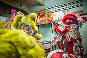 """10 FEBRUARY 2013 - BANGKOK, THAILAND: Lion Dancers perform in a small restaurant on Chinese New Year in the Chinatown section of Bangkok. Shop owners frequently invite Lion Dancers into the shops on the New Year to dance for a prosperous New Year. They then make a donation to the Lion Dance troupe. Bangkok has a large Chinese emigrant population, most of whom settled in Thailand in the 18th and 19th centuries. Chinese, or Lunar, New Year is celebrated with fireworks and parades in Chinese communities throughout Thailand. The coming year will be the """"Year of the Snake"""" in the Chinese zodiac.    PHOTO BY JACK KURTZ"""