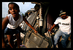 1 June, 2006. Lower 9th Ward, New Orleans, Louisiana. First day of hurricane season. Children of the storm return home. R/L; Arthur Murph clambers out of the rubble of what remains of his home. His daughters' friend Renisha Menendez (11 yrs) retrieves an evacuation suitcase he packed for his daughter Ariana, but was never able to get out before the home was destroyed. They stand in the wreckage of what used to be Murph and Ariana's home at 1739 Jourdan Ave in the devastated Lower 9th Ward. The huge barge which smashed through the original flood wall came to rest in front of their house, where a tidal wave of water rushed through, devastating the area where so many people died. Four of Arthur's neighbours perished in the storm. Arthur was in his home when the levee breached, he claims the night of the 28th August, 2005, the night before Hurricane Katrina made landfall. Arthur smashed his way out of his roof and swam to a neighbors house where he remained for 3 days awaiting rescue. Arthur can not go into details because of a pending lawsuit. He appears in the Spike Lee movie about the storm.