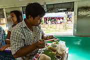 15 JUNE 2013 - YANGON, MYANMAR:  A betel vendor on the Yangon Circular Train. Many Burmese chew betel, a mildly stimulating leaf which stains the teeth red. The Yangon Circular Railway is the local commuter rail network that serves the Yangon metropolitan area. Operated by Myanmar Railways, the 45.9-kilometre (28.5 mi) 39-station loop system connects satellite towns and suburban areas to the city. The railway has about 200 coaches, runs 20 times and sells 100,000 to 150,000 tickets daily. The loop, which takes about three hours to complete, is a popular for tourists to see a cross section of life in Yangon. The trains from 3:45 am to 10:15 pm daily. The cost of a ticket for a distance of 15 miles is ten kyats (~nine US cents), and that for over 15 miles is twenty kyats (~18 US cents). Foreigners pay 1 USD (Kyat not accepted), regardless of the length of the journey.    PHOTO BY JACK KURTZ