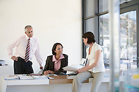 Three businesspeople in office having business meeting.