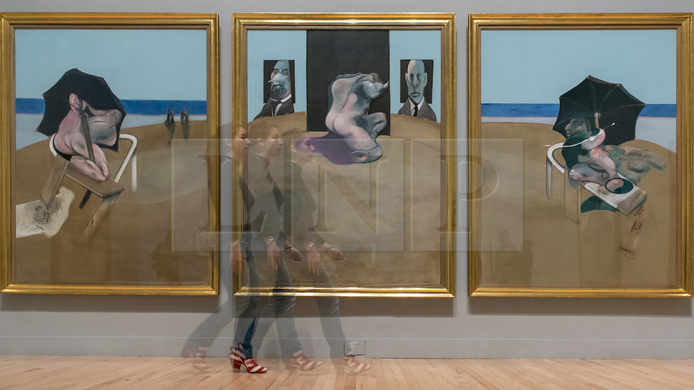 """© Licensed to London News Pictures. 26/02/2018. LONDON, UK. A multiple exposure of a staff member walking in front of """"Triptych"""", 1974-1977, by Francis Bacon.  Preview of """"All Too Human"""", an exhibition at Tate Britain which explores how artists in Britain have stretched the possibilities of paint in order to capture life around them.  The exhibition runs 28 February to 27 August 2018 and includes rarely seen works by Lucian Freud and Francis Bacon.  Photo credit: Stephen Chung/LNP"""