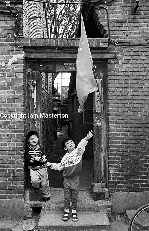 Children at entrance to old house in a hutong in Beijing China
