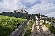 Walk or bike along an idyllic path in Selva di Val Gardena village beneath Langkofel/Sassolungo peak on your way to Vallunga, in the Dolomites, South Tyrol, Italy, Europe. The beautiful ski resort of Selva di Val Gardena (German: Wolkenstein in Gröden; Ladin: Sëlva Gherdëine) makes a great hiking base in the Dolomites, in the South Tyrol region (Trentino-Alto Adige/Südtirol) of Italy, Europe. For our favorite hike in the Dolomiti, start from Selva with the first morning bus to Ortisei, take the Seceda lift, admire great views up at the cross on the edge of Val di Funes (Villnöss), then walk 12 miles (2000 feet up, 5000 feet down) via the steep pass Furcela Forces De Sieles (Forcella Forces de Sielles) to beautiful Vallunga (trail #2 to 16), finishing where you started in Selva. The hike traverses the Geisler/Odle and Puez Groups from verdant pastures to alpine wonders, all preserved in a vast Nature Park: Parco Naturale Puez-Odle (German: Naturpark Puez-Geisler; Ladin: Parch Natural Pöz-Odles). UNESCO honored the Dolomites as a natural World Heritage Site in 2009.