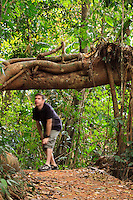 A young man walks through the thick rainforest on a 6km walk around Lake Barrine on the Atherton Tablelands in far north Queensland, Australia