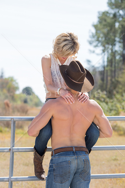 cowboy without a shirt and a girl sitting on a fence on a ranch together