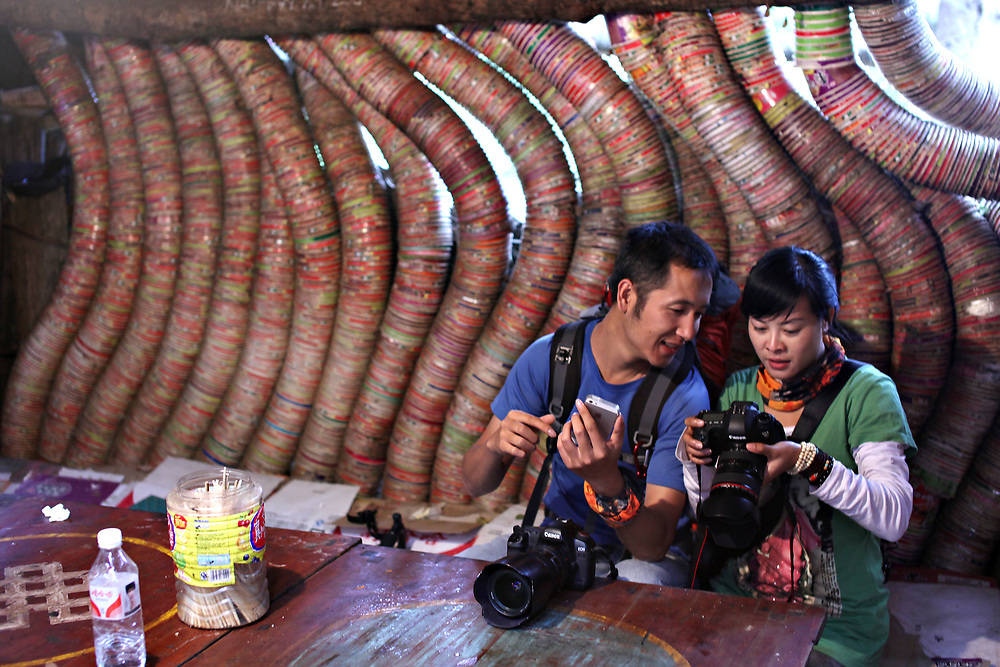 Hikers review their photos in a hut walled with used noodle bowls, Yunnan, China; September, 2013.