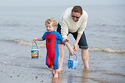 © Licensed to London News Pictures. 10/4/2015. Skegness, Lincolnshire, UK.<br /> People enjoying the warmest day of the year so far in the holiday resort of Skegness. Pictured, Isaac Barry (2) and his mum Vicki on the last day of a week long holiday in Skegness. Photo credit : Dave Warren/LNP