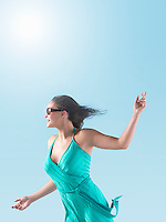 Woman in dress arms outstretched enjoying Sunshine side view