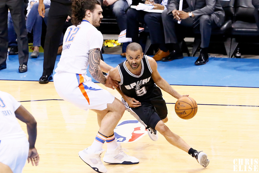 06 May 2016: San Antonio Spurs guard Tony Parker (9) drives past Oklahoma City Thunder center Steven Adams (12) during the San Antonio Spurs 100-96 victory over the Oklahoma City Thunder, during Game Three of the Western Conference Semifinals of the NBA Playoffs at the Chesapeake Energy Arena, Oklahoma City, Oklahoma, USA.