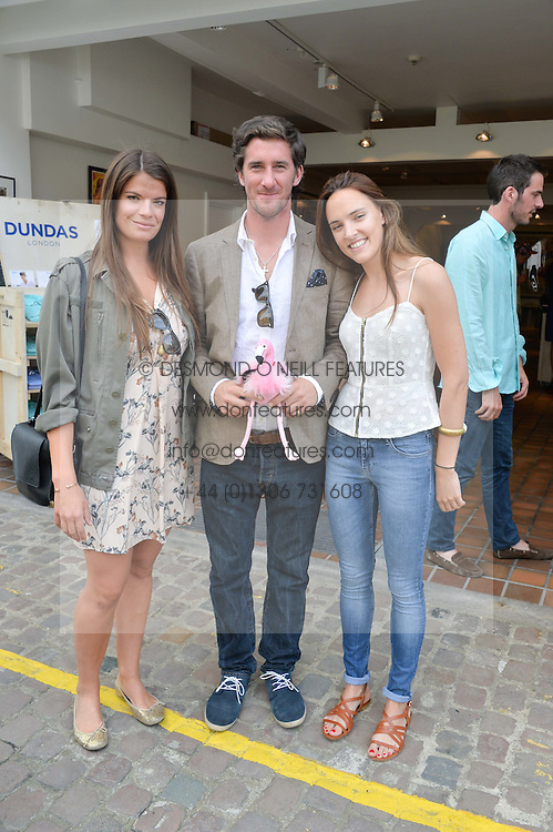 Left to right, MIRANDA RIGG, the 10th VISCOUNT MELVILLE and LUCINDA LOWE at the launch of Dundas London held at Fiskins Classic Car Showroom, 14 Queens Gate Place Mews, London on 25th June 2014.