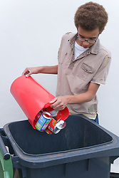 Teenage boy putting tins and cans into recycling wheelie bin ready for collection,