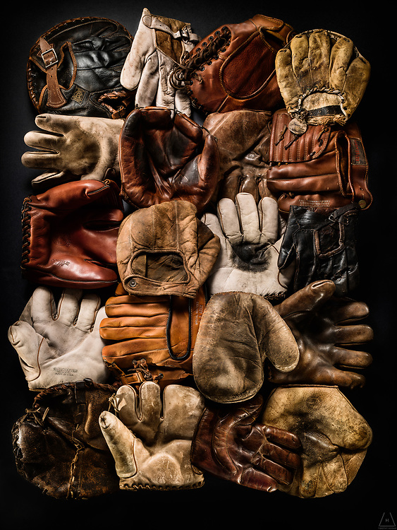 A group shot of vintage and antique baseball mitts, in mint condition, from various eras