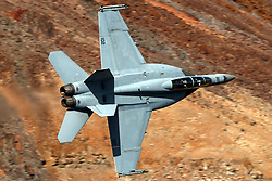 United States Navy Boeing F/A-18F Super Hornet (side 102) from the VFA-154 Black Knights squadron flies low level on the Jedi Transition through Star Wars Canyon / Rainbow Canyon, Death Valley National Park, Panamint Springs, California, United States of America