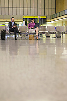 Business man and woman using laptop in airport lobby